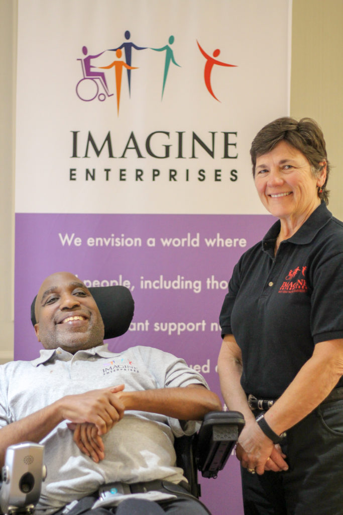 ricky peer mentor and norine executive director standing in front of Imagine banner